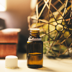 A bottle of essential oil sits on a table.